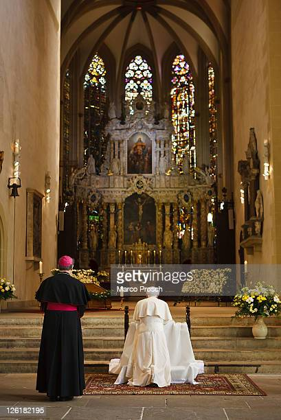 Pope Benedict XVI kneels to pray at the main altar of the Dom cathedral while Bishop Joachim Wanke stands next to him on September 23 2011 in Erfurt...