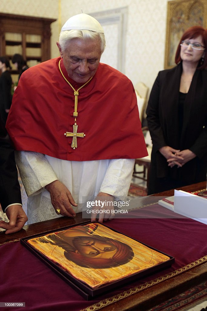 Pope Benedict XVI looks at a wooden icon of Jesus offered to him by Moldovan interim President Mihai Ghimpu (not pictured) on May 24, 2010 during a private audience in the pontiff's private library at the Vatican.