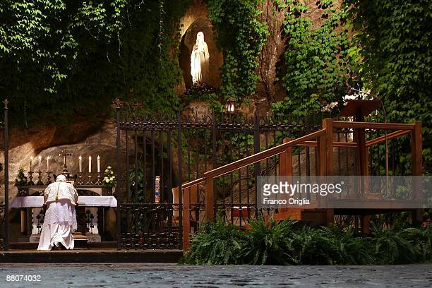 Pope Benedict XVI prays in front of the Lourdes grotto as he leads the ceremony at the Vatican gardens to conclude the Marian month on May 30 2009 in...