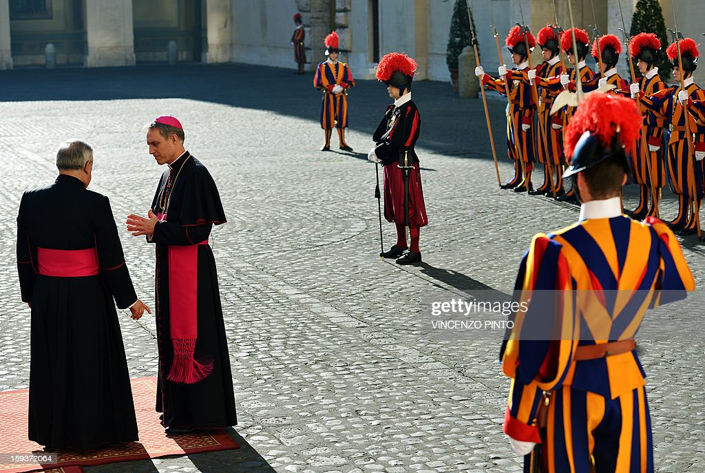 Pope Benedict XVI 's personal secretary Georg Gaenswein (C) talks with father Leonardo Sapienza (L) as he waits for Prince Albert II of Monaco and his wife Princess Charlene ahead of a private audience with the pontiff at the Vatican on January 12, 2013.