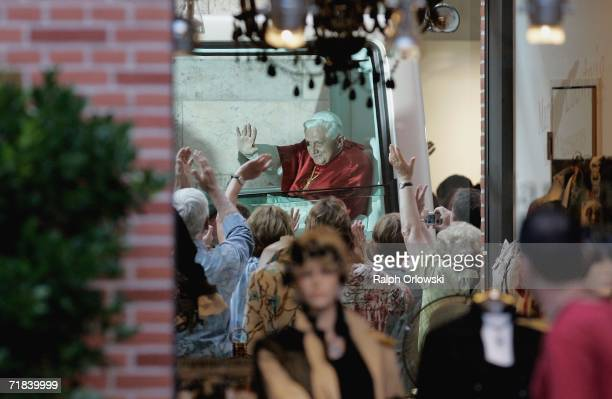 Pope Benedict XVI sitting in his popemobile is pictured through a shop window during his pastoral visit to his native Bavaria on September 10 2006 in...