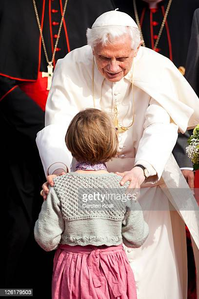 Pope Benedict XVI touchs 5years old Rebekka from the catholic kindergarten St Marien after his arrival on the airport on September 23 2011 in Erfurt...