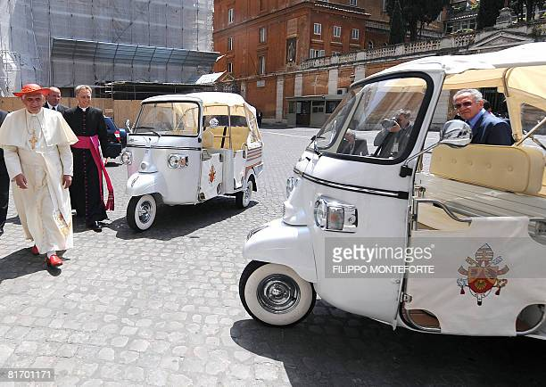 Pope Benedict XVI walks by to special models of Piaggio Ape offered to him after his weekly general audience in St Peter's Square at the Vatican on...