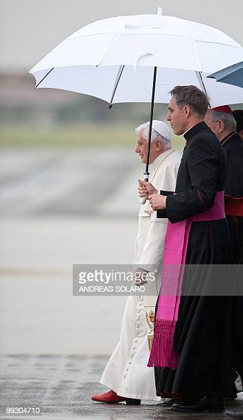 Pope Benedict XVI walks under an umbrella held by his personal secretary Georg Gaenswein as he disembarks from an Air Portugal plane at the end of...