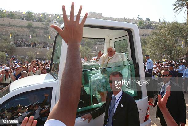 Pope Benedict XVI waves at the crowd from his Popemobile as he arrives to lead a mass at the Garden of Gethsemane at the foot of the Mount of Olives...