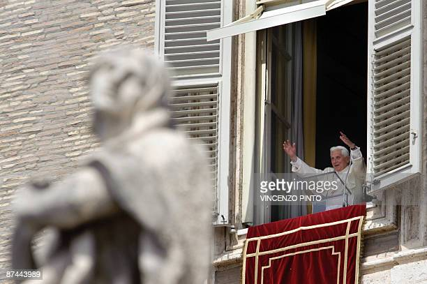 Pope Benedict XVI waves from the windows of his private appartments to pilgrims gathered in St Peter's square for his Sunday prayer on May 17 2009...