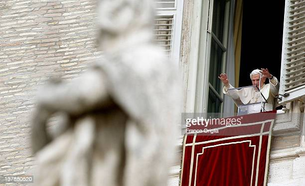 Pope Benedict XVI waves to the faithful gathered in St Peter's square from the window of his studio at the end of his Sunday Angelus prayer on...