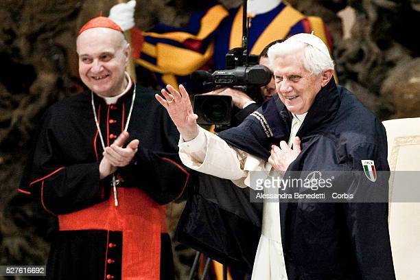 Pope Benedict XVI wearing a jacket of the Italian Civil Protection greets faithfuls at the end of a special audience with the agency's head Guido...