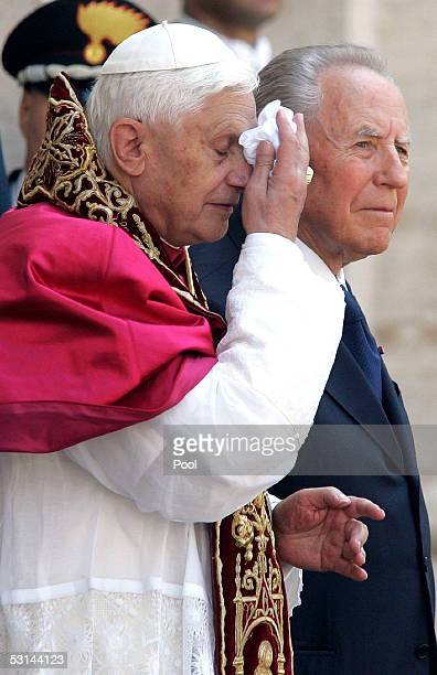 Pope Benedict XVI wipes his face while standing next to Italy's President Carlo Azeglio Ciampi during an official visit at the Quirinale Presidential...