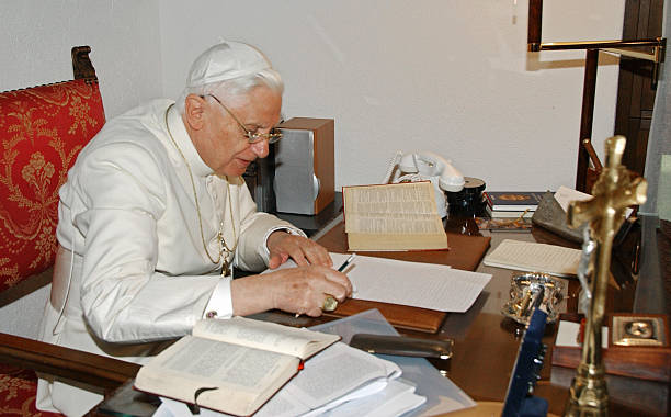 Pope Benedict Xvi Writes At His Desk In