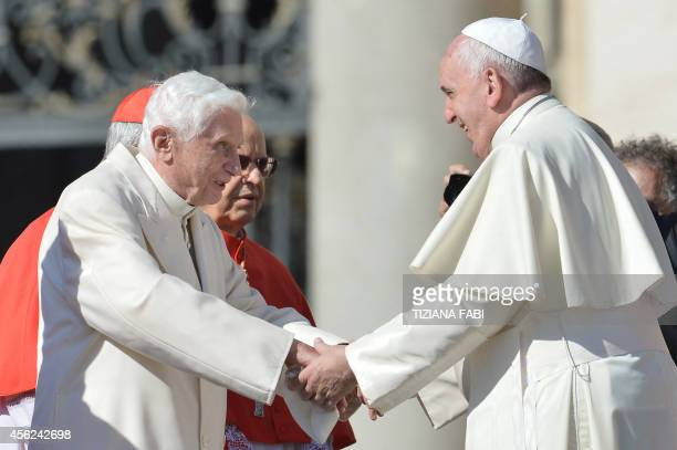 Pope emeritus Benedict XVI speaks with Pope Francis during a papal mass for elderly people at St Peter's square on September 28 2014 at the Vatican...