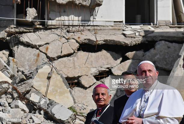 Pope Francis , accompanied by the Chaldean Catholic Archbishop of Mosul Najib Michaeel Moussa , looks on at a square near the ruins of the Syriac...