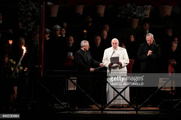 Pope Francis addresses the crowd during the Via Crucis torchlight procession at the Colosseum on Good Friday on March 30 2018 in Rome Christians...