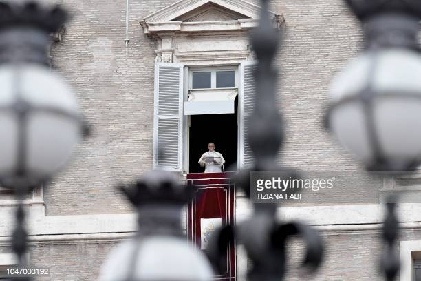 Pope Francis addresses the crowd from the window of the apostolic palace overlooking Saint Peter's square during his Sunday Angelus prayer on October...