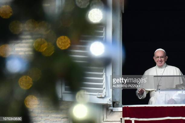 Pope Francis addresses the crowd from the window of the apostolic palace overlooking Saint Peter's square at The Vatican during his Sunday Angelus...