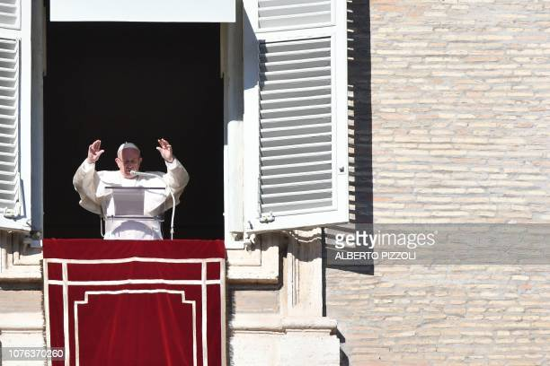 Pope Francis addresses the crowd from the window of the Apostolic palace overlooking St Peter's square during the New Year Angelus prayer in the...