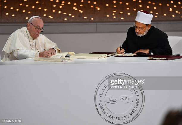Pope Francis and Egypt's Azhar Grand Imam Sheikh Ahmed alTayeb sign documents during the Human Fraternity Meeting at the Founders Memorial in Abu...