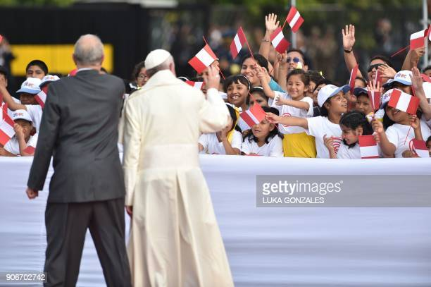 Pope Francis and Peruvian President Pedro Pablo Kuczynski wave to the faithful after the pope arrives at an air force base in Lima on January 18 2018...