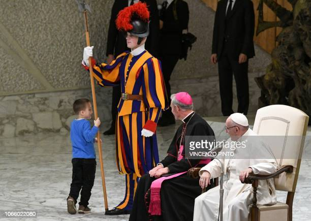 Pope Francis and Prefect of the Papal Household Georg Ganswein watch a boy who came from the audience onto the stage play with a Swiss Guard's spear...