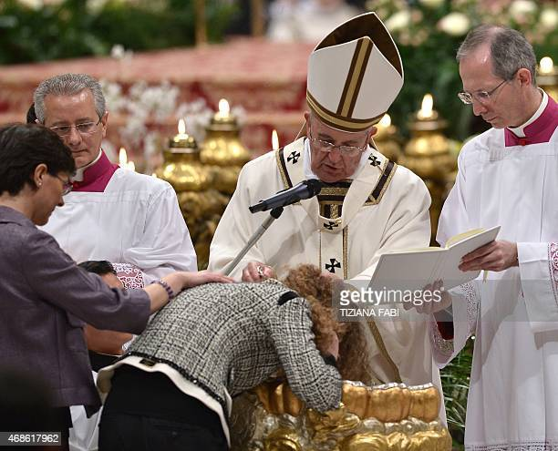 Pope Francis baptises a woman during the Easter Vigil at the St Peter's basilica on April 4 2015 in Vatican Christians around the world are marking...