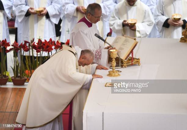 Pope Francis bends over the altar as he celebrates the Easter Sunday mass at St Peter's square on April 21 2019 in the Vatican Christians around the...