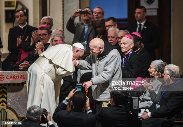 Pope Francis bends to kiss the hand of French Catholic monk Brother JeanPierre Schumacher the last survivor of the hostage taking of the seven monks...