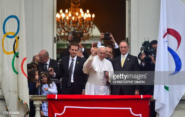 Pope Francis blesses the crowd from the balcony of the City Palace in Rio de Janeiro where he arrived to receive the keys of the city and bless the...