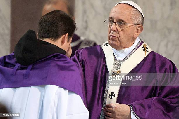 Pope Francis blesses with the ritual placing of ashes on the head of a member of the congregation during the Ash Wednesday service at the Santa...