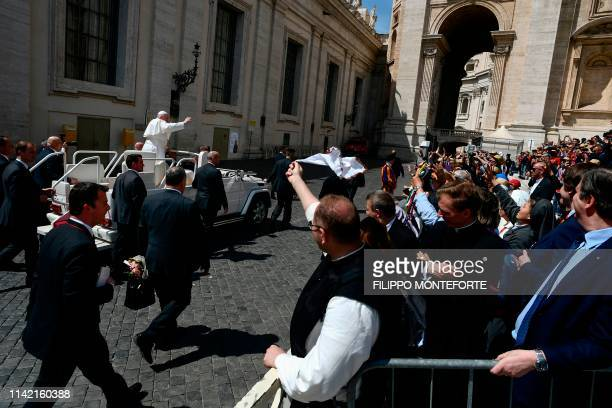 Pope Francis blesses worshipers as he leaves in the popemobile car at the end of the weekly general audience on May 8 2019 at St Peter's square in...