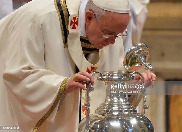 Pope Francis blows in an amphora containing holy oil during a Chrism mass for Maundy Thursday celebrating the Last Supper of Jesus and his disciples...