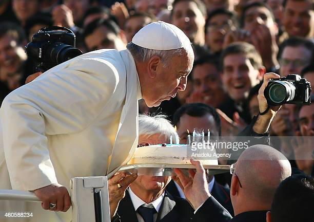 Pope Francis blows out the candles on his birthday cake during his general audience at St Peter's square on December 17 2014 at the Vatican City...