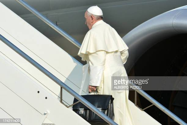 Pope Francis boards a plane on July 22 2013 at Rome's Fiumicino airport on his way to his first overseas trip to Brazil for World Youth Day AFP PHOTO...