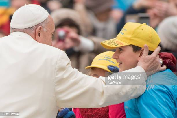 Pope Francis caresses a child as he arrives for his weekly general audience in Vatican Wednesday Feb 14 2018