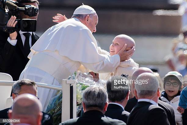 Pope Francis caresses a child as he is driven through the crowd ahead of his weekly general audience in St Peter's Square at the Vatican Wednesday...