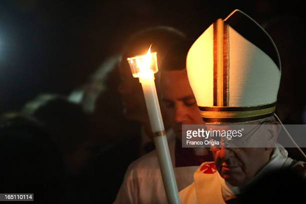 Pope Francis carries the Paschal candle as he leads the Ceremony of the Light during the Holy Saturday Easter vigil mass at St Peter's Basilica on...
