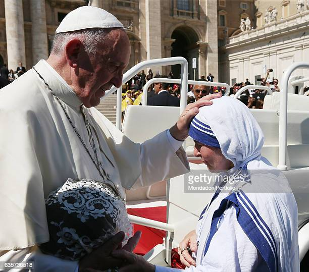 Pope Francis celebrating Holy Mass in St Peter's Square during the Mother Teresa Canonization Pope Francis placing a hand on the head of a sister of...