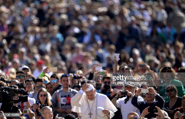 Pope Francis changes his zucchetto as he arrives for his weekly general audience in St Peter's square at the Vatican on April 22 2015 AFP PHOTO /...