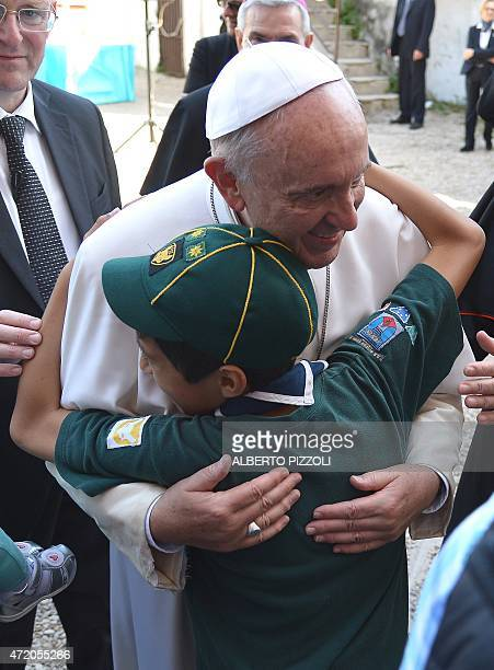 Pope Francis embraces a boy during his visit to the Santa Maria Regina Pacis church on May 3 2015 in Ostiah south of Rome AFP PHOTO / ALBERTO PIZZOLI