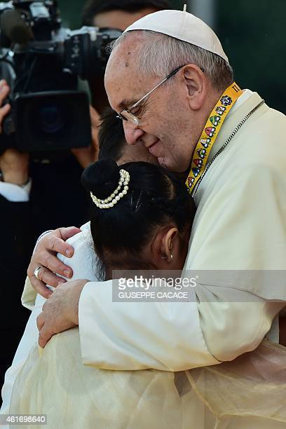 Pope Francis embraces two children including 12yearold Glyzelle Palomar during his visit to the University of Santo Tomas in Manila on January 18...