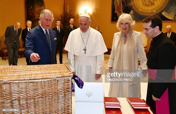 Pope Francis exchanges gifts with Britain's Prince Charles Prince of Wales and his wife Camilla Duchess of Cornwall during a private audience on...