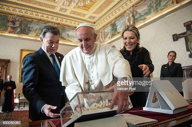 Pope Francis exchanges gifts with Colombia President Juan Manuel Santos Calderon and wife Maria Clemencia Rodriguez de Santos during an audience at...