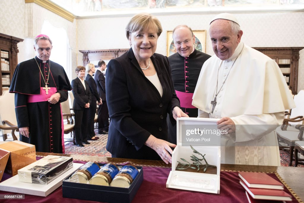 Pope Francis exchanges gifts with German Chancellor Angela Merkel at his private library in the Apostolic Palace on June 17, 2017 in Vatican City, Vatican. During the meeting Issues of common interest were addressed, with special regard for the upcoming G20 meeting in Hamburg, and the parties agreed on the need to dedicate special attention to the responsibility of the international community in combating poverty and hunger, the global threat of terrorism, and climate change.