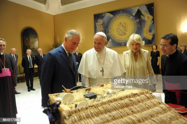 Pope Francis exchanges gifts with Prince Charles Prince of Wales and Camilla Duchess of Cornwall during an audience on April 4 2017 in Vatican City...