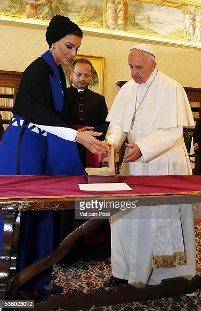 Pope Francis exchanges gifts with Sheikha Mozah bint Nasser Al Missned at his private library in the Apostolic Palace on June 4 2016 in Vatican City...