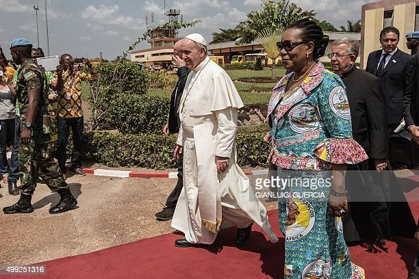 Pope Francis , flanked by Central African Republic interim president Catherine Samba-Panza walks to board a plane to leave at the Mpoko International...