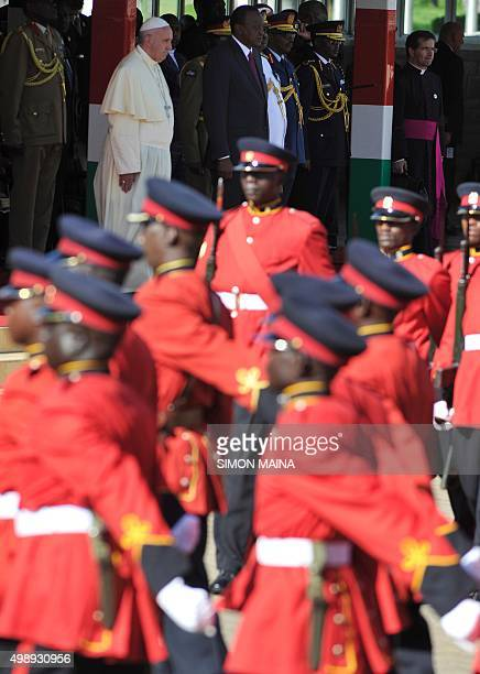 Pope Francis flanked by Kenya President Uhuru Kenyatta watches a military parade before boarding his plane on November 27 2015 in Nairobi on his way...