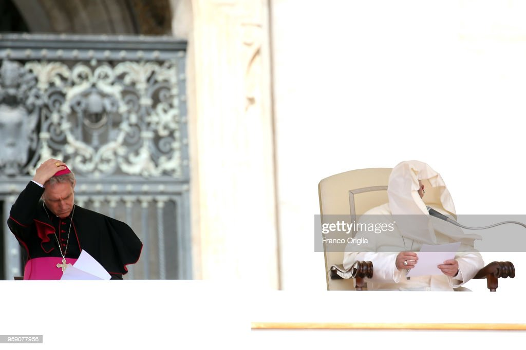 Pope Francis, flanked by Prefect of the papal household Georg Gaenswein (L), holds his homily as a gust of wind catches his mantle during his weekly audience in St. Peter's square on May 16, 2018 in Vatican City, Vatican. Addressing pilgrims in St Peter's Square for the weekly Wednesday General Audience, Pope Francis made an appeal for peace in the Holy Land, Middle East.