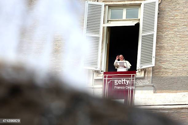 Pope Francis framed by a fountain delivers his Angelus blessing from the window of the former Papal apartments overlooking St Peter's Square on...