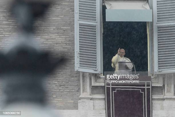 Pope Francis gestures as he delivers his message to the faithful during the weekly Angelus prayer on November 25 2018 as rain pours over St Peter's...