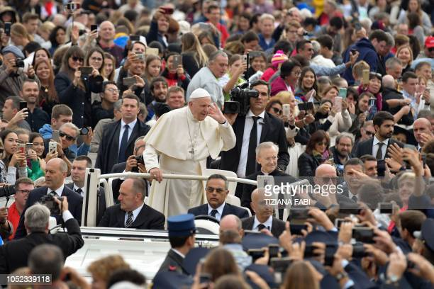 TOPSHOT Pope Francis gestures towards the faithful as he arrives on the popemobile car for the weekly general audience on October 17 2018 at St...
